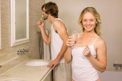采取与她的男朋友的白肤金发的妇女一个药片刷他的牙 图库摄影