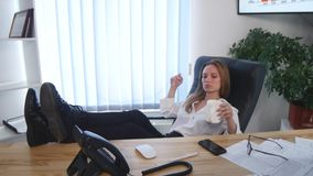采取与她的赤脚的办公室工作者一个咖啡休息在书桌和一个杯子上在她的手上上升了浓咖啡 图库摄影