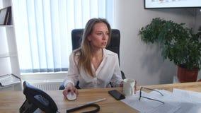 采取与她的赤脚的办公室工作者一个咖啡休息在书桌和一个杯子上在她的手上上升了浓咖啡 免版税库存图片
