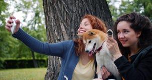 采取与小狗的学生的慢动作selfie在公园使用智能手机照相机 股票录像