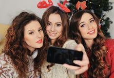 采取与巧妙的电话的三个女朋友一selfie 库存照片
