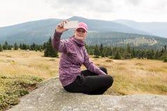 采取与巧妙的电话的妇女远足者照片selfie在山 免版税库存图片