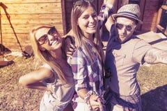采取与巧妙的电话的小组微笑的朋友滑稽的selfie 库存照片