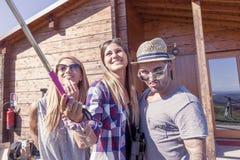 采取与巧妙的电话的小组微笑的朋友滑稽的selfie 免版税库存图片