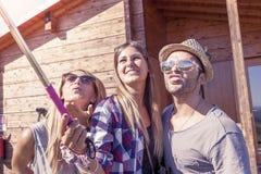采取与巧妙的电话的小组微笑的朋友滑稽的selfie 图库摄影