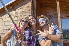 采取与巧妙的电话的小组微笑的朋友滑稽的selfie 免版税库存照片