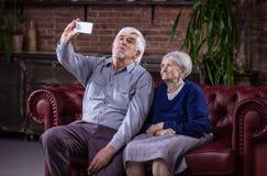 采取与巧妙的电话的资深夫妇selfie 免版税图库摄影