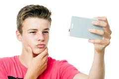 采取与巧妙的电话的青少年的男孩自画象 库存照片