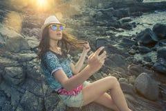 采取与巧妙的电话的年轻深色的妇女selfie在岩石coa 库存照片
