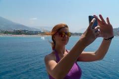 采取与手机的可爱的女孩一张selfie画象在小船,微笑 免版税库存图片