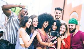 采取与手机的多种族朋友录影selfie在被稳定的常平架-获得的年轻人在新的技术趋向的乐趣 图库摄影