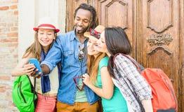 采取与手机的小组愉快的多种族朋友selfie 库存图片