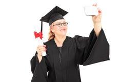 采取与手机的成熟女性毕业生一selfie 免版税库存图片