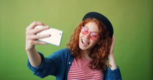 采取与智能手机挥动的手微笑的十几岁的女孩画象selfie 股票录像