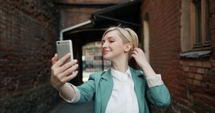 采取与智能手机照相机的俏丽的金发碧眼的女人的慢动作selfie户外 影视素材
