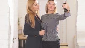 采取与智能手机的两个美丽的无忧无虑的女孩selfie 影视素材
