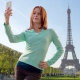 采取与智能手机的俏丽的女孩Selfie在巴黎 库存照片