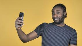 采取与智能手机的偶然非洲人Selfie隔绝在黄色背景 股票录像