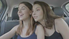 采取与智能手机的千福年的妇女selfie坐一辆旅行汽车的后座在假日旅途上的- 股票视频