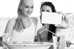 采取与智能手机的女性朋友一selfie 库存照片
