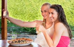 采取与智能手机的女性朋友一selfie 免版税库存图片