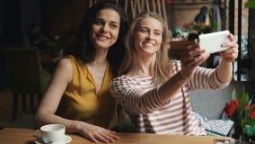 采取与智能手机的女朋友selfie做滑稽的面孔在咖啡厅 股票录像