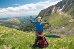 采取与智能手机的妇女远足者selfie在山 免版税库存照片
