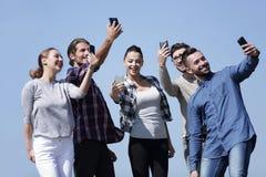 采取与智能手机的小组学生selfie 图库摄影