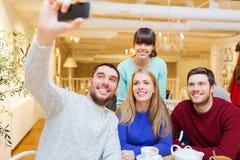 采取与智能手机的小组朋友selfie 库存图片