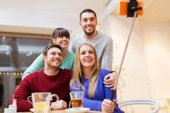 采取与智能手机的小组朋友selfie 免版税库存图片