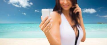 采取与智能手机的少妇selfie在海滩 免版税库存照片