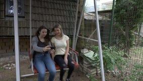 采取与智能手机的少年女性朋友一selfie,当他们摇摆的室外一起放松在摇篮-时 股票录像