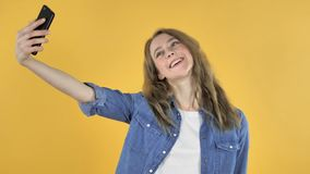 采取与智能手机的年轻俏丽的女孩Selfie在黄色背景 影视素材