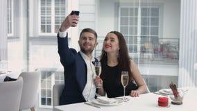 采取与智能手机的快乐的夫妇一幽默selfie在餐馆 免版税库存照片
