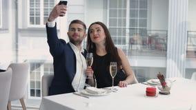 采取与智能手机的快乐的夫妇一幽默selfie在餐馆 免版税库存图片