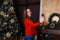 采取与智能手机的快乐的少妇圣诞节selfie 免版税库存照片