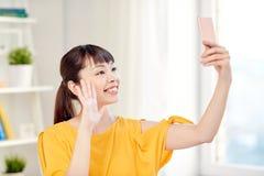采取与智能手机的愉快的亚裔妇女selfie 图库摄影