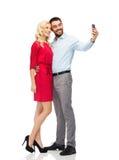 采取与智能手机的愉快的夫妇selfie 免版税库存图片