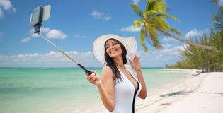 采取与智能手机的愉快的妇女selfie在海滩 图库摄影