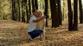 采取与智能手机的愉快的家庭selfie在秋天公园 库存照片
