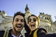 采取与智能手机的愉快的旅行夫妇selfie在la威尼斯广场,罗马,意大利的著名地标 免版税库存照片