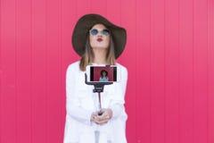 采取与智能手机的愉快的美丽的妇女一selfie在红色b 免版税库存图片