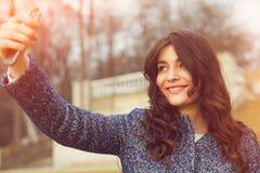 采取与智能手机的美丽的时兴的女孩一selfie 免版税库存照片