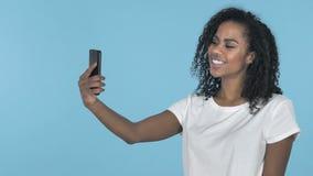 采取与智能手机的非洲女孩Selfie隔绝在蓝色背景 股票录像