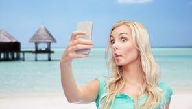采取与智能手机的滑稽的少妇selfie 库存图片
