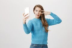 采取与智能手机的selfie,做逗人喜爱的面孔和显示和平或胜利姿态的时兴的时髦白种人妇女 免版税库存照片