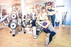 采取与流动智能手机的小组嬉戏年轻女人selfie在健身房健身房锻炼-愉快的运动的人在举重房 库存照片