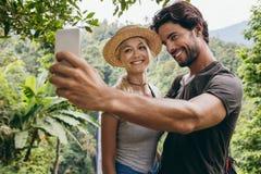 采取与瀑布的微笑的年轻夫妇selfie 免版税库存图片