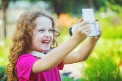 采取与照片照相机的笑的小女孩selfie 免版税库存图片