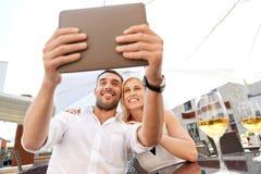 采取与片剂个人计算机的愉快的夫妇selfie在咖啡馆 图库摄影